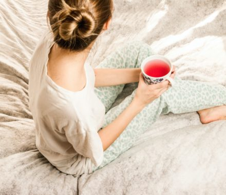 woman sat on bed with tea